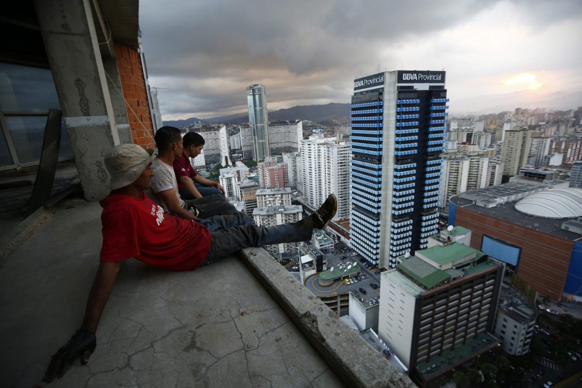 """Men rest after salvaging metal on the 30th floor of the """"Tower of David"""" skyscraper in Caracas"""