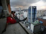 Men rest after salvaging metal on the 30th floor of the